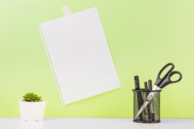 Different pens and scissors in holder near blank paper stucked on wall