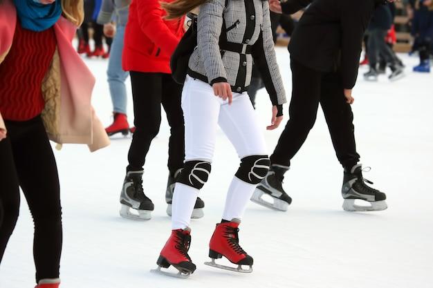 다른 사람들이 아이스 링크에서 활발하게 스케이트를 타고 있습니다. 취미와 여가. 동계 스포츠