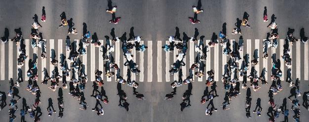街のパノラマの横断歩道でさまざまな人々がシマウマの歩行者用駐車場で人々を撃ちました...