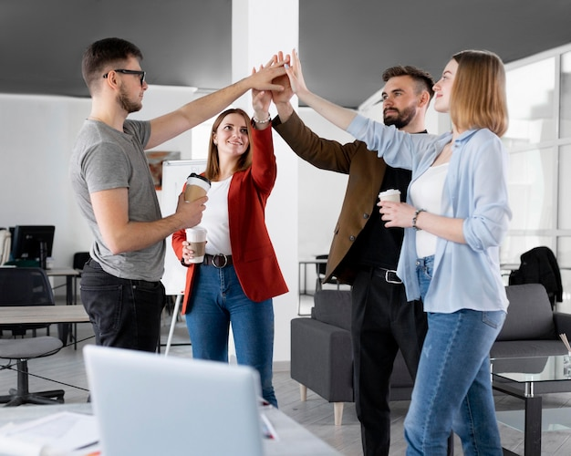 Diverse persone si danno il cinque al lavoro