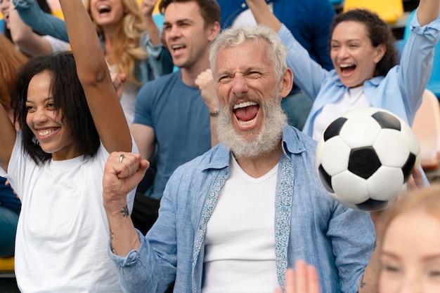 Разные люди смотрят на футбольную команду