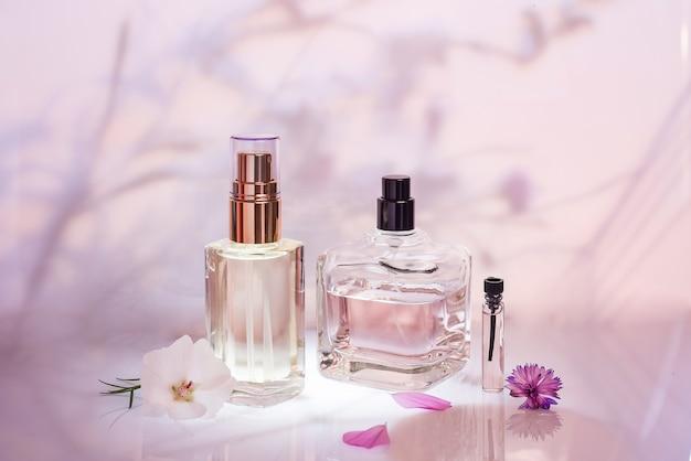 ピンクの背景に植物とさまざまな香水瓶とサンプラー