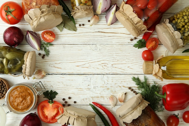 Different pickled food and ingredients on white wooden table