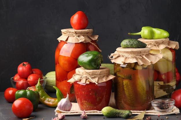 Различные маринованные овощи в стеклянных банках для длительного хранения