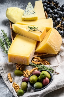 Different pieces of cheese with nuts olives and grapes. assorted delicious snacks. top view