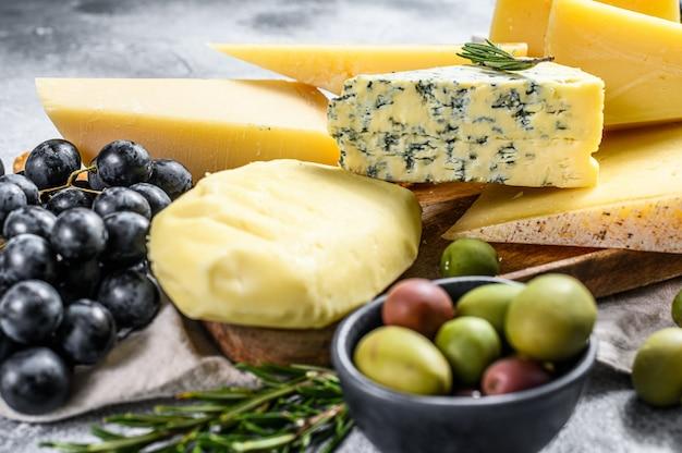 Различные кусочки сыра с орехами, оливками и виноградом. ассорти вкусных закусок. серая стена. вид сверху