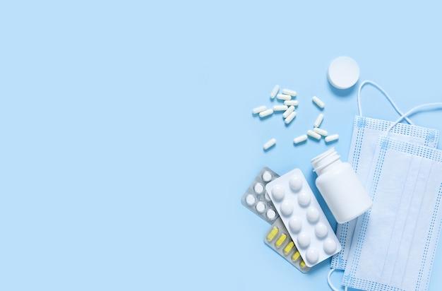 Различные таблетки и маска для лица на синем фоне. здравоохранение. категорически.