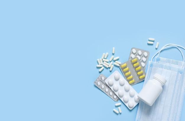 Различные таблетки, антисептик и маска для лица на синем фоне. здравоохранение. категорически.