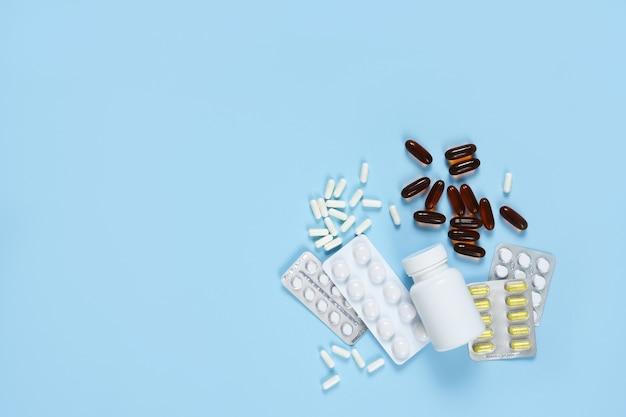Различные таблетки на синем фоне. здравоохранение. категорически.