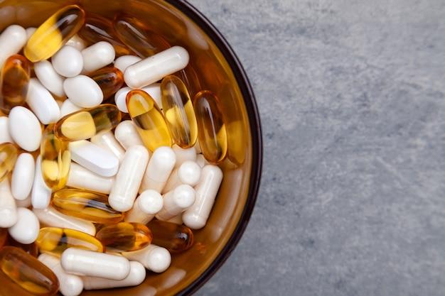 Разные таблетки на коричневом стекле