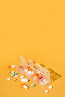 Разные таблетки на желтом фоне