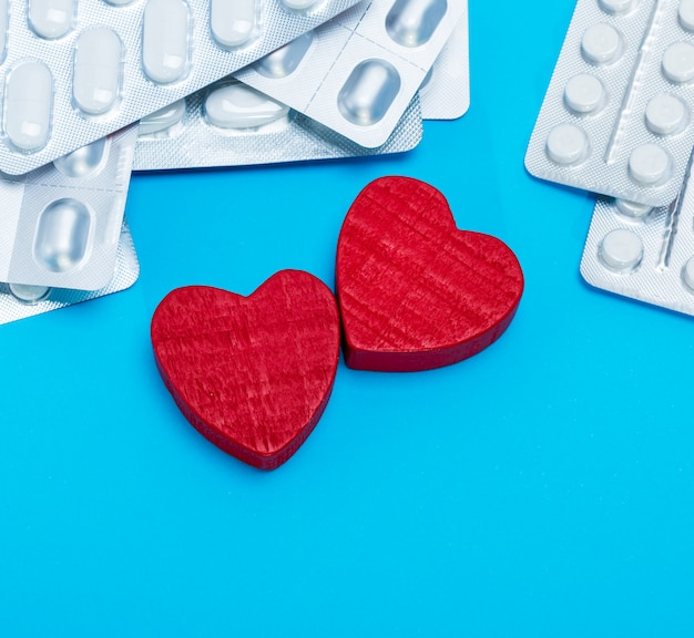 Different pills in a package and two red hearts