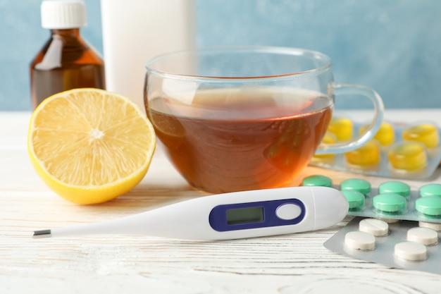 別の薬、温度計、医療ボトル、お茶、白い木製のテーブル、クローズアップのレモン