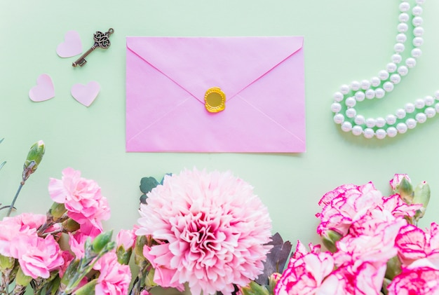 Different pink flowers with envelope on green table