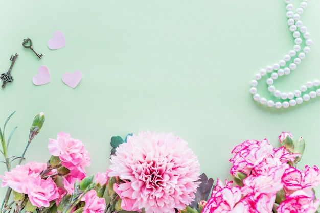 Different pink flowers with hearts on green table