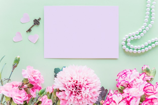 Different pink flowers with paper on green table