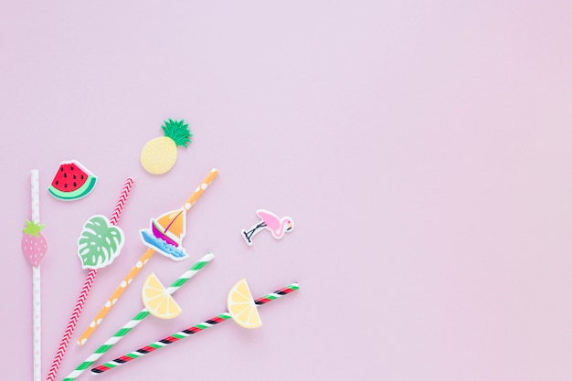 Different plastic straws on pink table