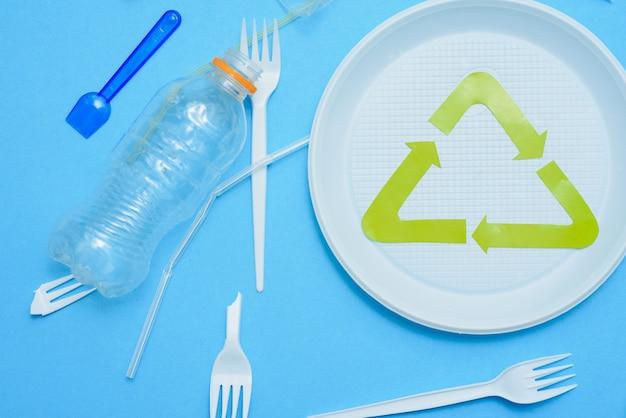 Различный пластиковый мусор и знак переработки мусора на цветном фоне сверху