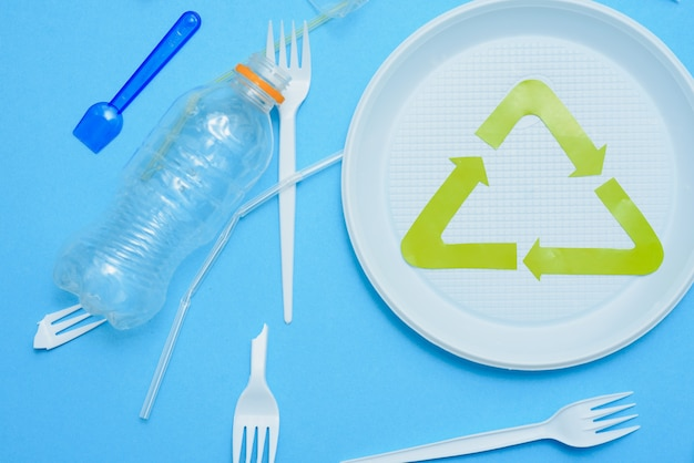 Different plastic trash and garbage recycling sign on a colored background top view