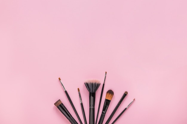 Different powder brushes on pink table