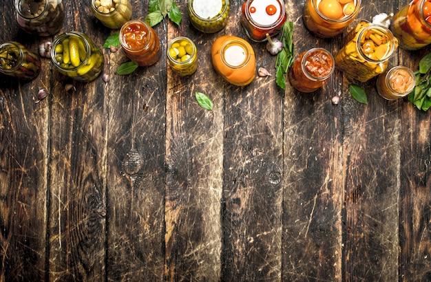 ガラスの瓶に入った野菜やキノコとは異なる保存野菜。木製の背景に。