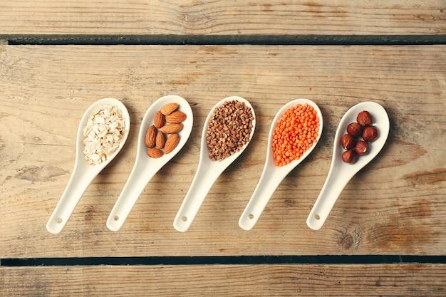 Различные продукты в ложках на деревянном столе крупным планом