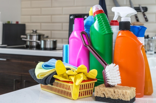 Different products and items for cleaning on the countertop in the kitchen.