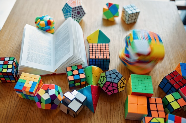 Different puzzle cubes and opened book on the table, nobody. toy for brain and logical mind training, creative game, solving of complex problems