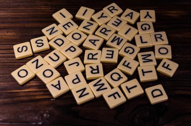 素朴な木製のテーブルの異なるランダムな文字