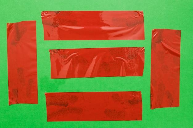 Различные красные ленты на зеленой стене