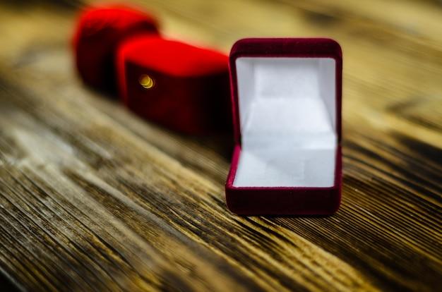 나무 테이블에 다른 빨간 벨벳 보석 상자