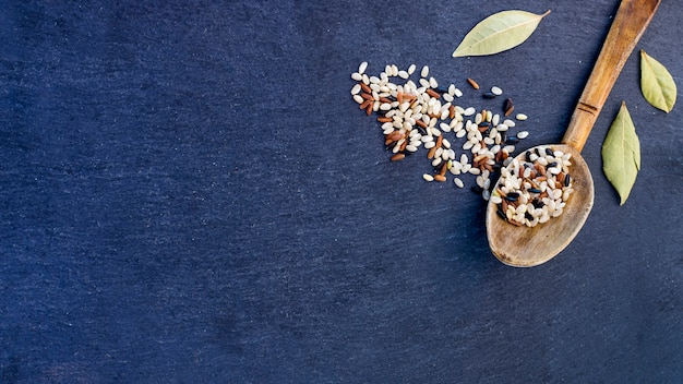 Different rice grains in wooden spoon on blue table