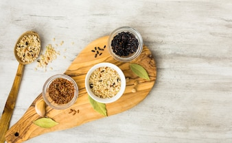 Different rice types in bowls on wooden board with spoon