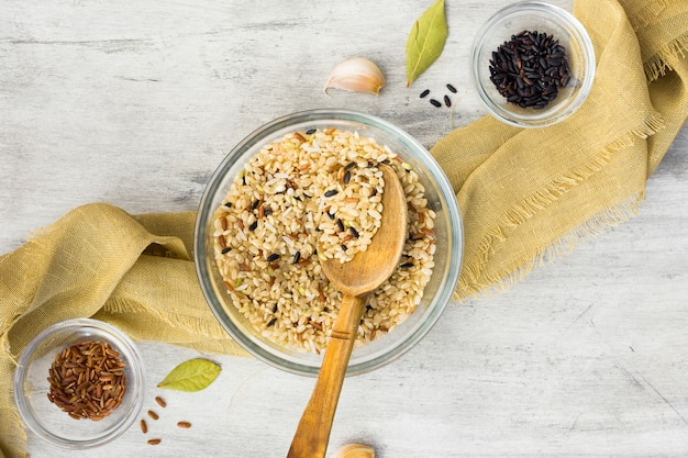 Различные виды риса в мисках с ложкой на столе