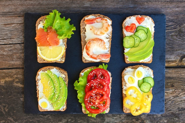 Of different sandwiches on the old wooden background. top view. flat lay.