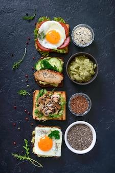 Различные бутерброды на черном столе. вкусная здоровая закуска с авокадо. быстрые завтраки. концепция здорового питания. правильное питание. вид сверху
