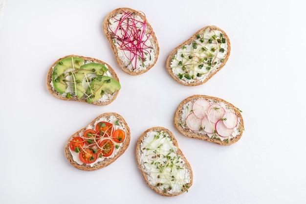 Различные бутерброды с микрогринами и овощами на белом фоне