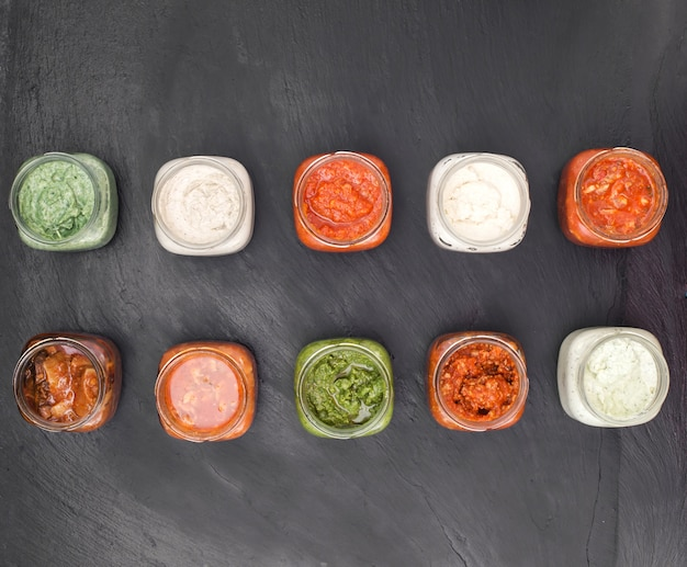 Different sauces in glass jar top view