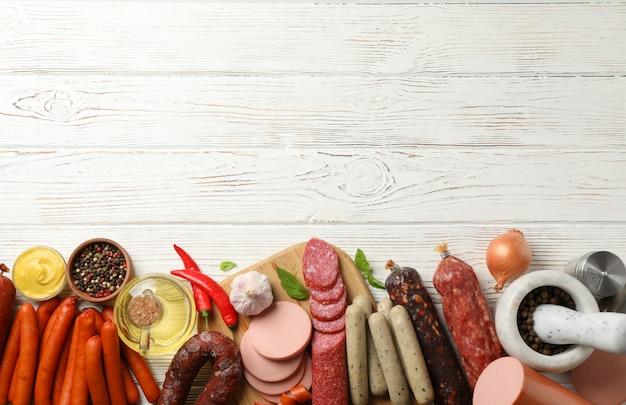 Различные колбасы и специи на деревянном, место для текста
