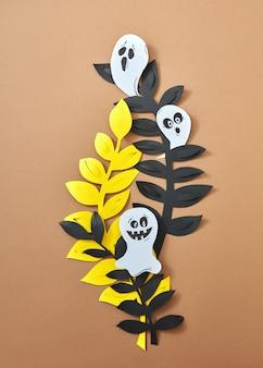 Различные страшные призраки на листьях бумажных ветвей представлены на коричневом фоне с копией пространства. бумажная композиция ручной работы к хэллоуину. плоская планировка