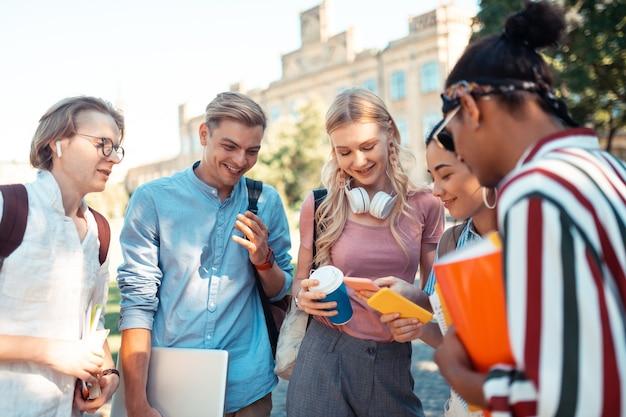 Разные графики. две улыбающиеся девушки смотрят на свои смартфоны и сравнивают свое расписание на глазах у веселых одноклассников.