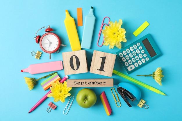 Различные школьные принадлежности и деревянный календарь на синем