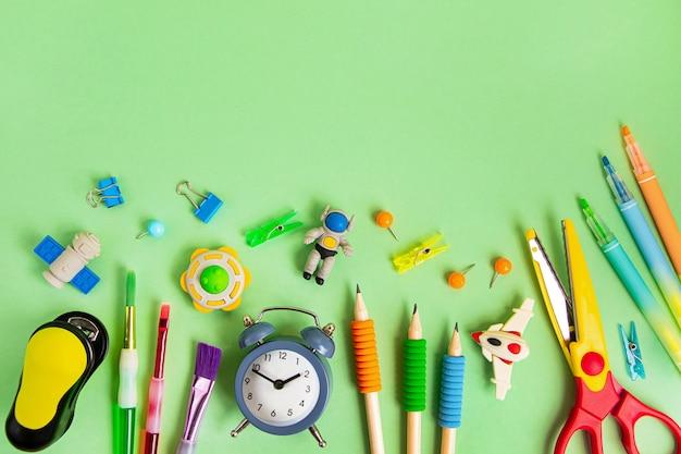 Различные школьные принадлежности на зеленом фоне. обратно в школу концепции, вид сверху.