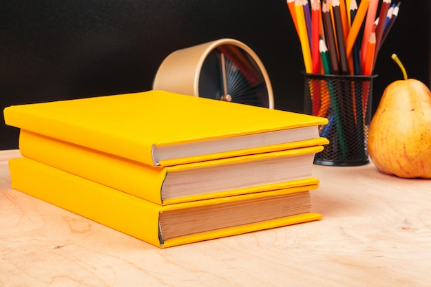 Different school supplies,  books and pear on wooden table