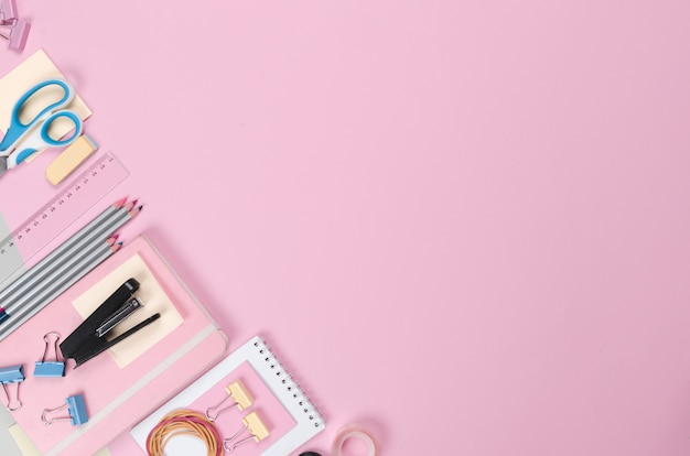 Different school supplies on light pink background