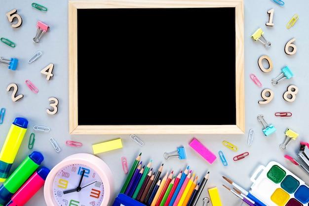 Различные школьные принадлежности с рамкой для текста. обратно в школу. вид сверху