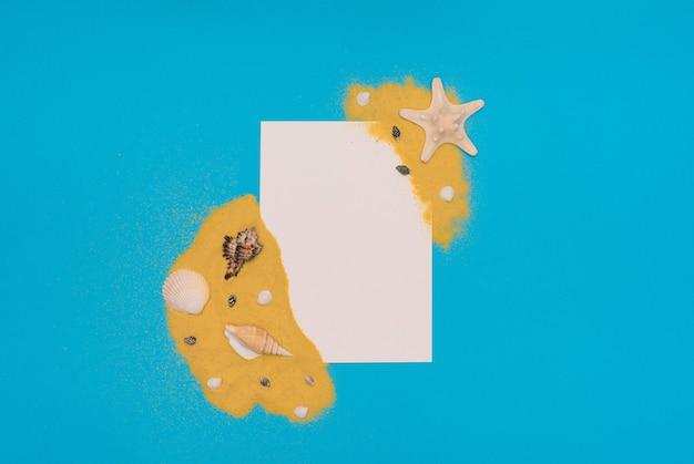 파란색 배경에 흰색 종이 카드 메모와 함께 밝은 노란색 모래에 다른 바다 조개와 불가사리. 여름 시간 개념입니다. 복사 공간이 있는 플랫 레이 스타일.