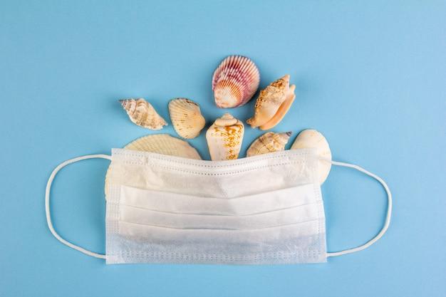 青い背景の上面図の医療マスクの下のさまざまな貝殻