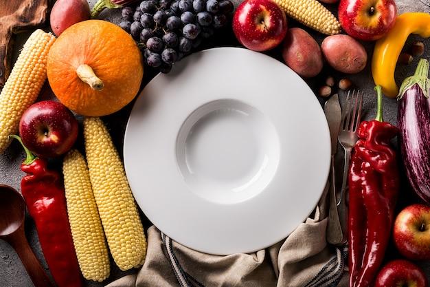 別の季節の秋の野菜と果物、灰色の背景に空のプレート