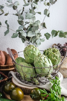 Different seasonal vegetables and artichokes in a metal basket